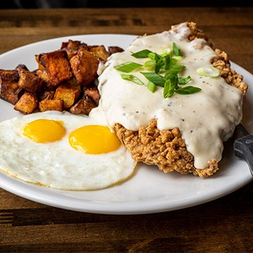 Bruncheonette Chicken Fried Steak topped with Country Gravy, Country Potato Medley, and 2 Eggs your way