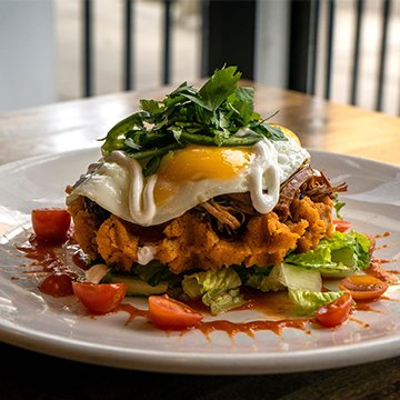 Bruncheonette Tamale Waffle Green Onion & Cheddar Tamale Waffle, Mexican Spiced Shredded Beef, Cherry Tomatoes, Pickled Jalapeños, Romaine, Crema, and 2 Eggs